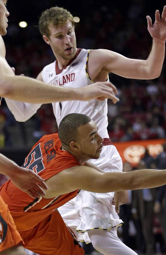 Oregon State guard Roberto Nelson, center, tries to keep possession of the ball as he falls between teammate Angus Brandt, left, and Maryland forward Evan Smotrycz during the second half of an NCAA college basketball game in College Park, Md., Sunday, Nov. 17, 2013