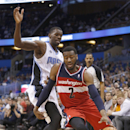 Washington Wizards guard John Wall (2) drives past Orlando Magic center Dewayne Dedmon during the first half of an NBA basketball game in Orlando, Fla., Friday, Apr. 11, 2014 The Associated Press