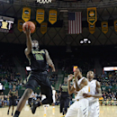 Baylor forward Taurean Prince (21) drives past West Virginia guard Tarik Phillip, center, and guard Daxter Miles Jr., right, in the first half of an NCAA college basketball game, Saturday, Feb. 28, 2015, in Waco, Texas. Baylor won 78-66. (AP Photo/Rod Aydelotte)