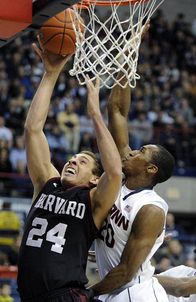 Harvard's Jonah Travis (24) drives past Connecticut's Lasan Kromah (20) during the first half of an NCAA college basketball game in Storrs, Conn., Wednesday, Jan. 8, 2014