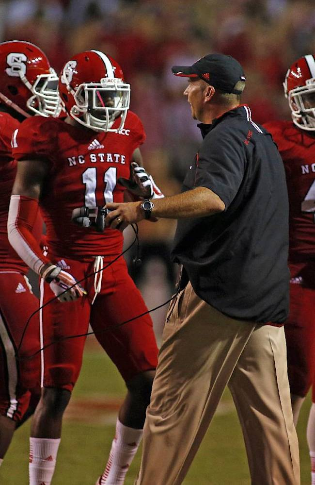 North Carolina State head coach Dave Doeren, center, congratulates his team after stopping Clemson during the first half of an NCAA college football game in Raleigh, N.C., Thursday, Sept. 19, 2013. Clemson won 26-14