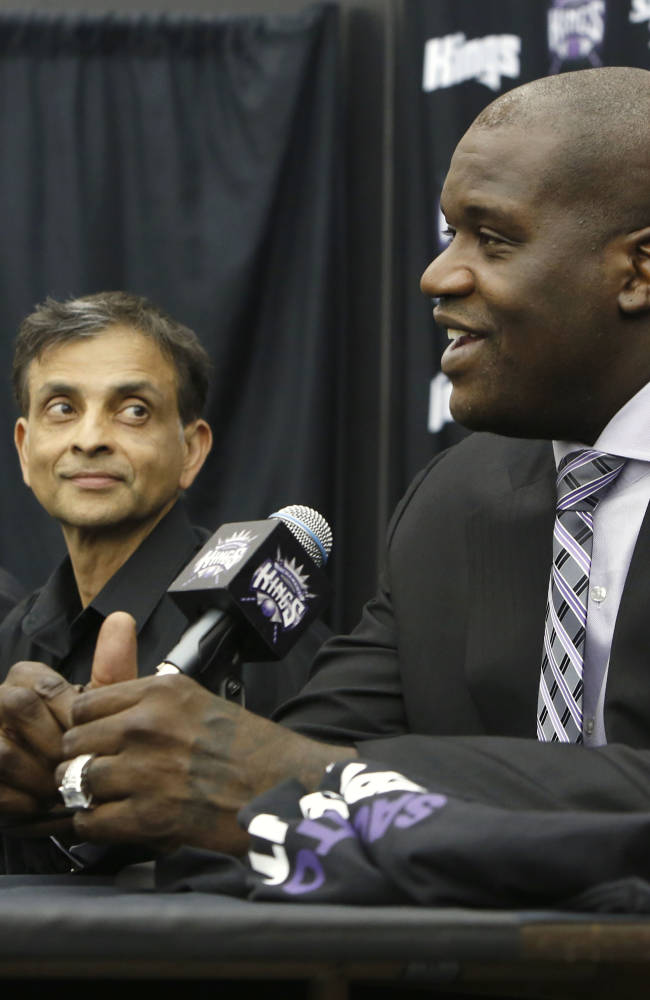 File- In this Sept. 24, 2013 file photo,  Shaquille O'Neal smiles during a news conference where he was welcomed as one of the new minority owners of the Sacramento Kings in Sacramento, Calif., as majority owners Vivek Ranadive, center, and Mark Mastrov, left, look on.  Ranadive added O'Neal to the ownership group and has asked the former Los Angeles Laker's center to mentor the Kings center, DeMarcus Cousins
