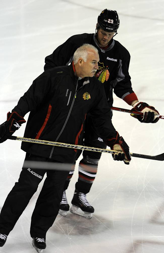 Chicago Blackhawks coach Joel Quenneville, front, talks with Bryan Bickell at the teams NHL hockey training camp on the campus of the University of Notre Dame in South Bend, Ind., Thursday, Sept. 12, 2013