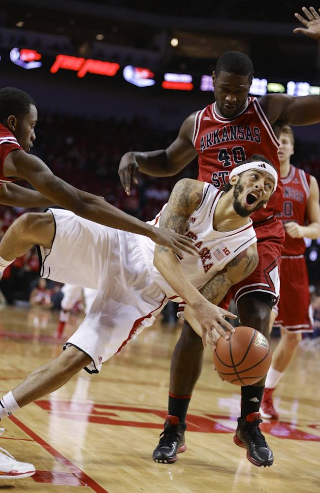 Nebraska's Terran Petteway (5) tries to shoot while losing his footing against the defense of Arkansas State's Cameron Golden, left, and Kendrick Washington (40) in the second half of an NCAA college basketball game in Lincoln, Neb., Saturday, Dec. 14, 2013. Nebraska won 79-67