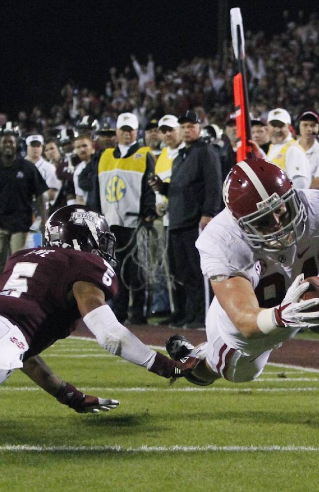 Alabama tight end Brian Vogler (84) dives into the end zone past Mississippi State defensive back Jamerson Love (5) for an 18-yard touchdown reception during the second quarter of an NCAA college football game, Saturday, Nov. 16, 2013, in Starkville, Miss