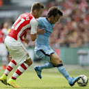 Arsenal's Calum Chambers, left, challenges Manchester City's David Silva during the English FA Community Shield soccer match at Wembley Stadium, London Sunday, Aug. 10, 2014