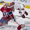 Phoenix Coyotes' Tim Kennedy flips next to Montreal Canadiens goalie Carey Price during the third period of an NHL hockey game Tuesday, Dec. 17, 2013, in Montreal. (AP Photo/The Canadian Press, Paul Chiasson)