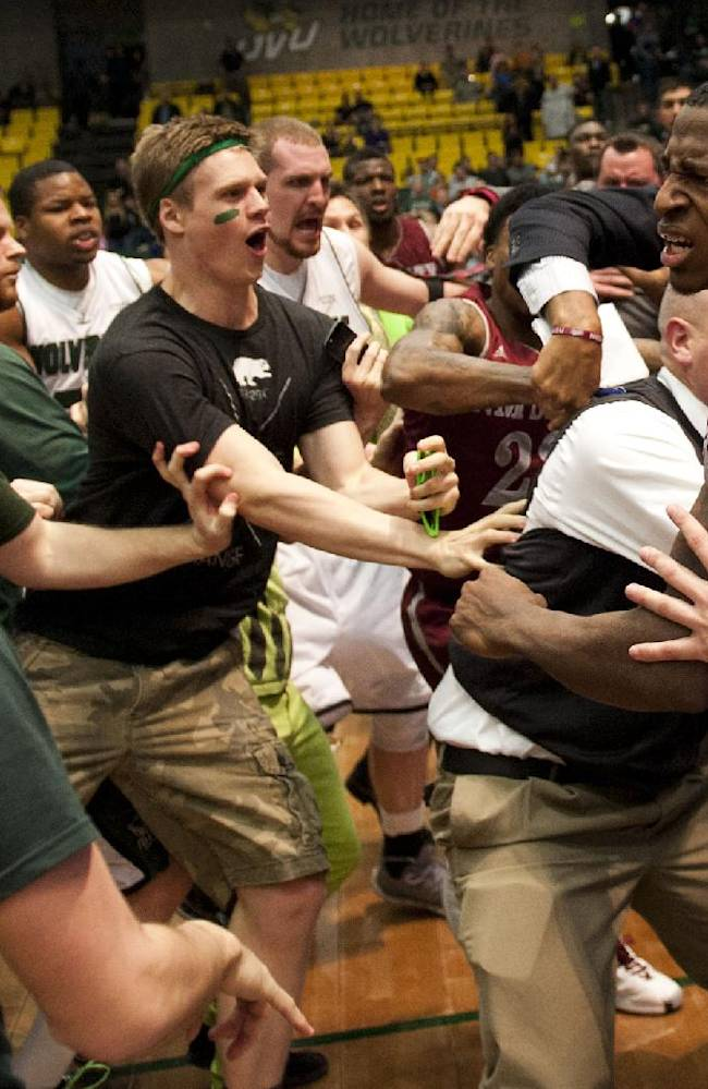 In this Thursday, Feb. 27, 2014 photo, New Mexico State's DK Eldridge, at right in red and white uniform, is held by security during  a brawl involving players and fans who came onto the court when New Mexico State guard K.C. Ross-Miller hurled the ball at Utah Valley's Holton Hunsaker seconds after the Wolverines' 66-61 overtime victory against the Aggies in Orem, Utah