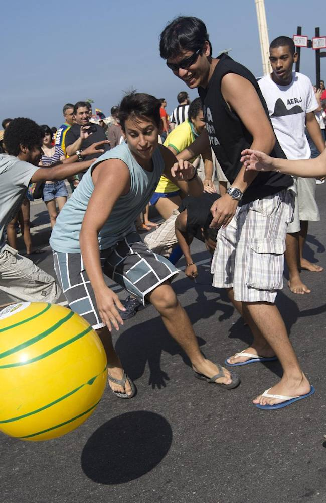 Demonstrators play soccer while they protest against the money spent on the World Cup and demand better public services, on Copacabana beach in Rio de Janeiro, Brazil, Friday, July 4, 2014