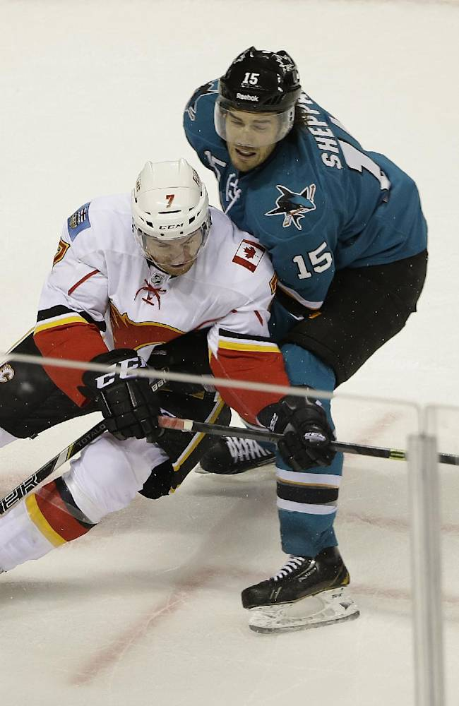 Calgary Flames defenseman T.J. Brodie, left, and San Jose Sharks center James Sheppard, right, vie for the puck during the second period of an NHL hockey game Saturday, Oct. 19, 2013, in San Jose, Calif
