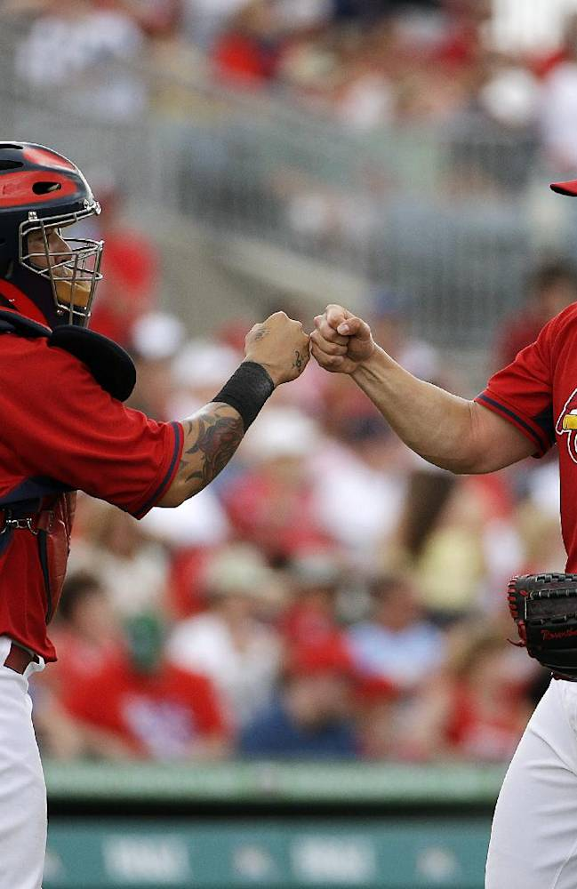 St. Louis Cardinals relief pitcher Trevor Rosenthal, right, fist-bumps catcher Yadier Molina after closing out the ninth inning of an exhibition spring training baseball game against the Washington Nationals, Friday, March 21, 2014, in Jupiter, Fla