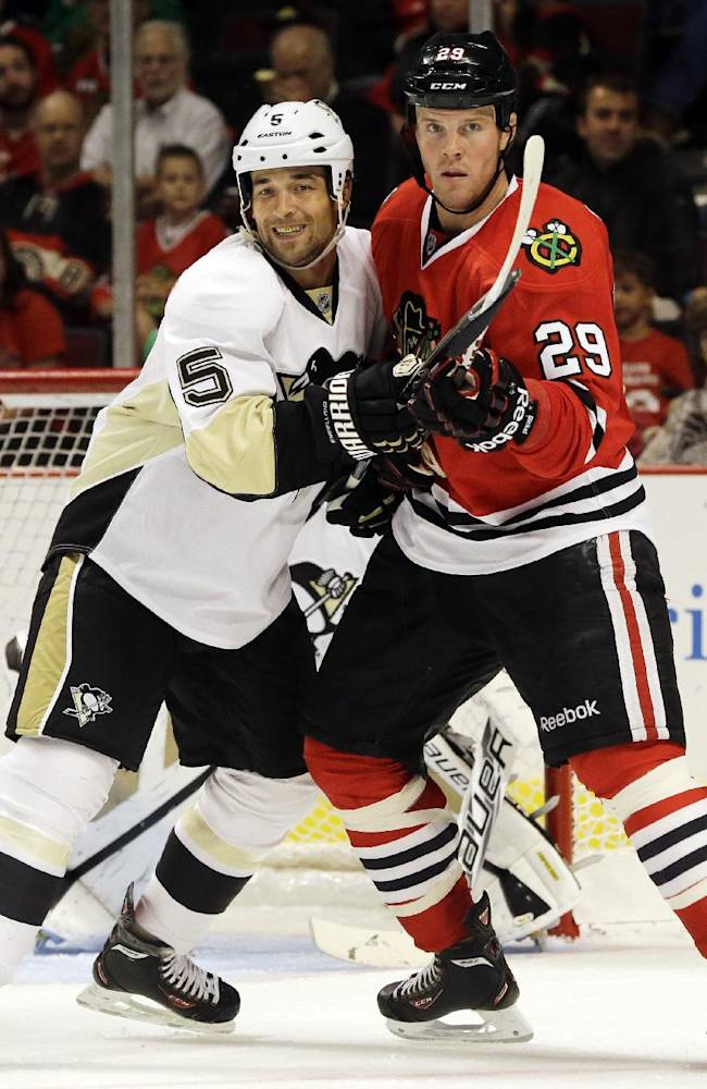 Pittsburgh Penguins' Deryk Engelland, left, and Chicago Blackhawks' Bryan Bickell battle as they wait for the puck during the second period of an NHL preseason hockey game in Chicago, Thursday, Sept. 19, 2013