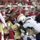 San Francisco 49ers running back Frank Gore (21) runs past San Diego Chargers outside linebacker Melvin Ingram to score on a 52-yard touchdown run during the first quarter of an NFL football game in Santa Clara, Calif., Saturday, Dec. 20, 2014. (AP Photo/Marcio Jose Sanchez)
