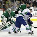 Dallas Stars defenseman Jordie Benn (24) prevents Vancouver Canucks' Daniel Sedin (22) of Sweden from controlling the puck as Stars goalie Kari Lehtonen watches during the second period of an NHL hockey game, Thursday, Dec. 19, 2013, in Dallas. (AP Photo/Tony Gutierrez)