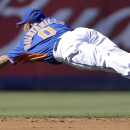 New York Mets shortstop Omar Quintanilla dives but cannot reach a ball hit for a single by Miami Marlins' Jeff Baker during the sixth inning of an exhibition spring training baseball game Saturday, March 1, 2014, in Port St. Lucie, Fla The Associated Pres