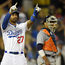 Los Angeles Dodgers' Matt Kemp, left, gestures toward Dee Gordon at first as Detroit Tigers catcher Victor Martinez looks on during the ninth inning of a baseball game, Wednesday, April 9, 2014, in Los Angeles. Kemp scored on a single by Gordon The Associ