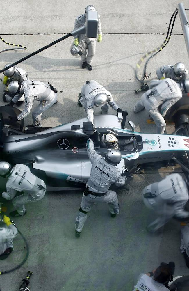 The pit crew for Mercedes driver Lewis Hamilton of Britain change his tires during the Malaysian Formula One Grand Prix at Sepang International Circuit in Sepang, Malaysia, Sunday, March 30, 2014