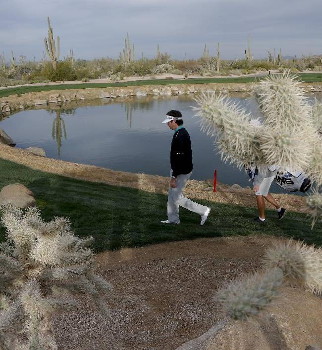 Bubba Watson walks to the fourth hole in his match against Mikko Ilonen, of Finland, during the first round of the Match Play Championship golf tournament on Wednesday, Feb. 19, 2014, in Marana, Ariz