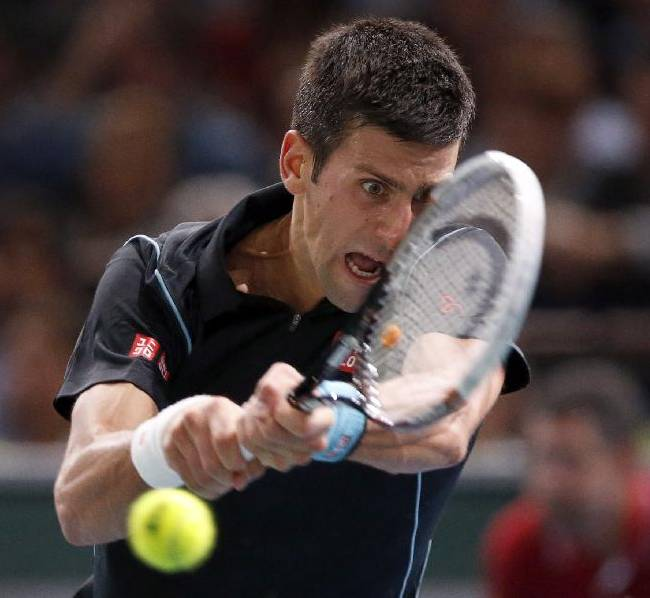 Novak Djokovic of Serbia returns the ball to Roger Federer of Switzerland during their semi final match, at the Paris Masters tennis at Bercy Arena in Paris, France, Saturday, Nov. 2, 2013