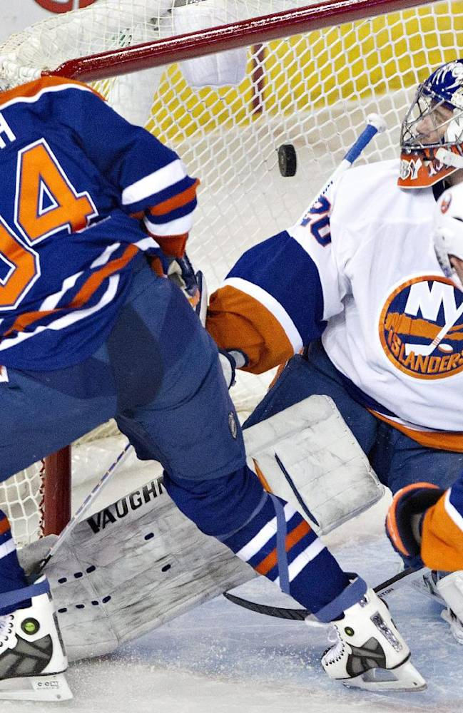 New York Islanders goalie Evgeni Nabokov (20) watches the puck go in the net on a shot from Edmonton Oilers' Ryan Smyth (94) as Thomas Hickey (14) chases during third period NHL hockey action in Edmonton, Alberta, on Thursday March 6, 2014