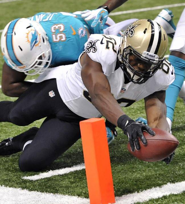 New Orleans Saints tight end Benjamin Watson (82) reaches over the pylon to score a touchdown as Miami Dolphins' Jelani Jenkins (53) attempts the tackle in the second half of an NFL football game in New Orleans, Monday, Sept. 30, 2013