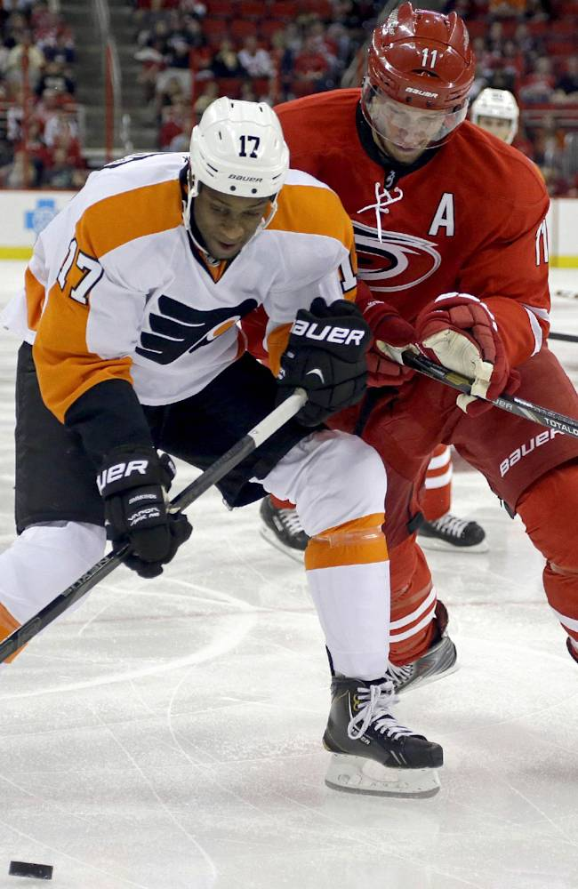 Philadelphia Flyers' Wayne Simmonds (17) and Carolina Hurricanes' Jordan Staal (11) chase the puck during the first period of an NHL hockey game in Raleigh, N.C., Sunday, Oct. 6, 2013