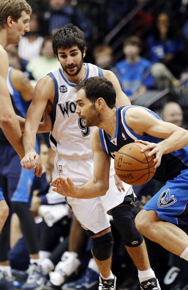 Dallas Mavericks' Jose Calderon, right, of Spain, drives by Minnesota Timberwolves' Ricky Rubio, of Spain, as Dallas Mavericks' Dirk Nowitzki, left, of Germany, tries to block Rubio in the first quarter of an NBA basketball game, Monday, Dec. 30, 2013, in Minneapolis