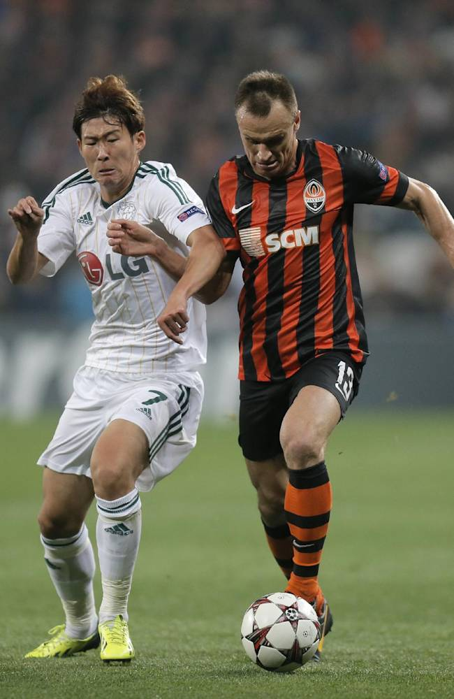 Donetsk's  Vyacheslav Shevchuk, right, and Leverkusen's  Son Heung-min Son challenge for the ball during the Champions League group A soccer match between Bayer 04 Leverkusen and FC Shakhtar Donetsk  at the Donbas Arena stadium in Donetsk, Ukraine, Tuesday, Nov. 5, 2013