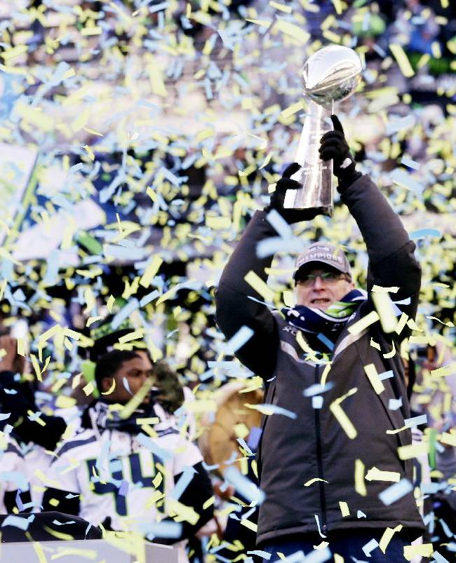 CORRECTS BYLINE TO ELAINE THOMPSON NOT TED WARREN - Seattle Seahawks owner Paul Allen lifts the Vince Lombardi Trophy during a rally on Wednesday, Feb. 5, 2014, in Seattle. The Seahawks defeated the Denver Broncos on Sunday in NFL football's Super Bowl XLVIII game in East Rutherford, N.J