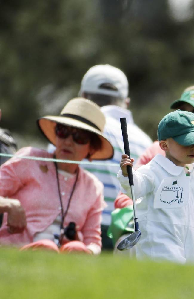 Scott Stallings's son Finn carries his golf club during the par three competition at the Masters golf tournament Wednesday, April 9, 2014, in Augusta, Ga
