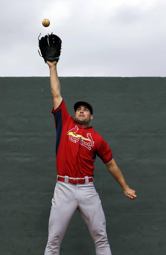 St. Louis Cardinals pitcher Tyler Lyons reaches for a ball hit to him against a wall during a drill at spring training baseball practice Friday, Feb. 21, 2014, in Jupiter, Fla