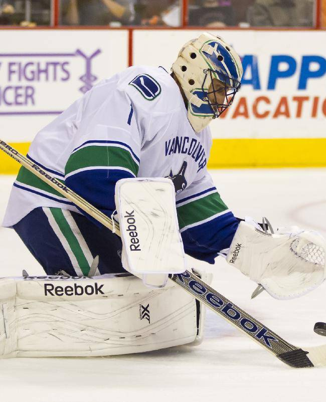 Vancouver Canucks' Roberto Luongo looks to cover up the loose puck during the second period of an NHL hockey game against the Philadelphia Flyers, Tuesday, Oct. 15, 2013, in Philadelphia