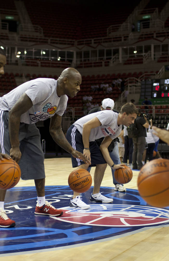 Washington Wizards guard John Wall, left, and free agent pickup Al Harrington, second left, go over dribbling techniques with kids attending a NBA Cares basketball clinic, in Rio de Janeiro, Brazil, Thursday, Oct. 10, 2013. The Wizards are in Brazil preparing for NBA's first exhibition game in South America against the Chicago Bulls on Saturday