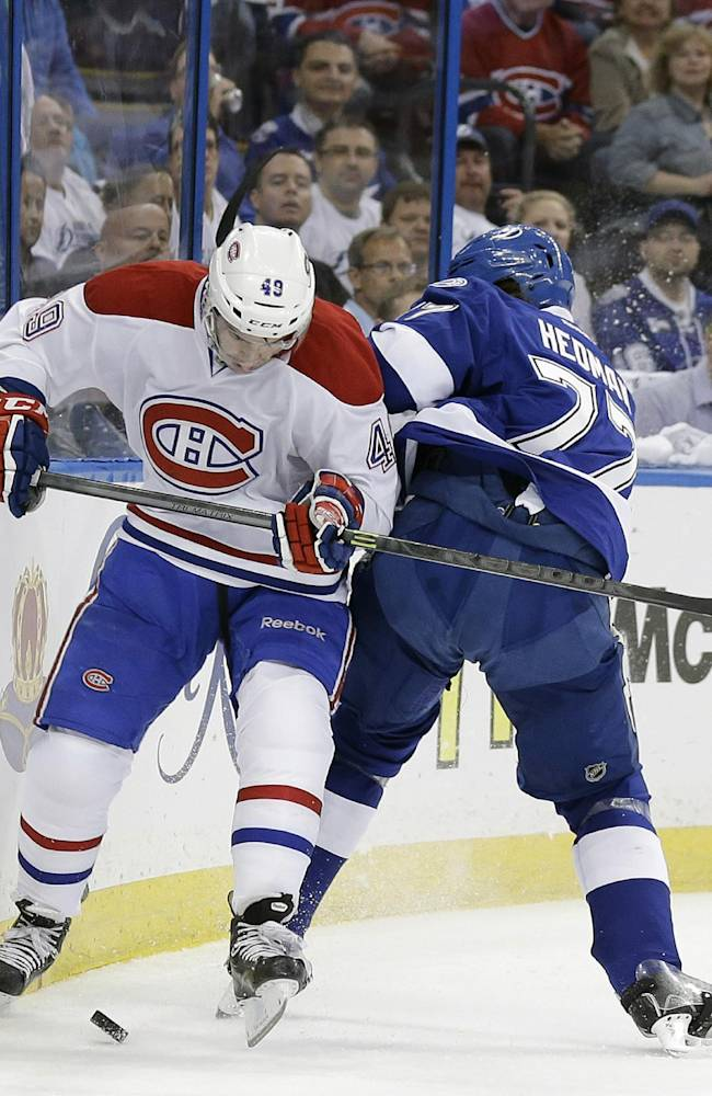 Montreal Canadiens left wing Michael Bournival (49) goes around a check by Tampa Bay Lightning defenseman Victor Hedman (77), of Sweden, during the first period of Game 2 of a first-round NHL hockey playoff series on 2Friday, April 18, 2014, in Tampa, Fla
