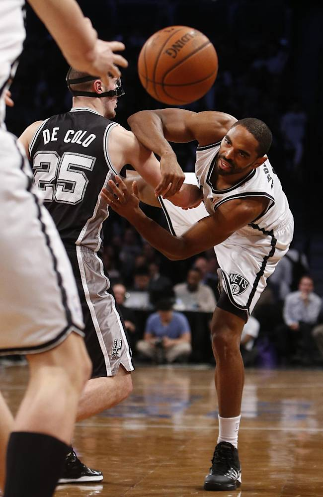 Brooklyn Nets' Alan Anderson, right, loses his balance while passing away from San Antonio Spurs' Nando De Colo (25), of France, during the second half of an NBA basketball game on Thursday, Feb. 6, 2014, in New York.  Brooklyn won 103-89