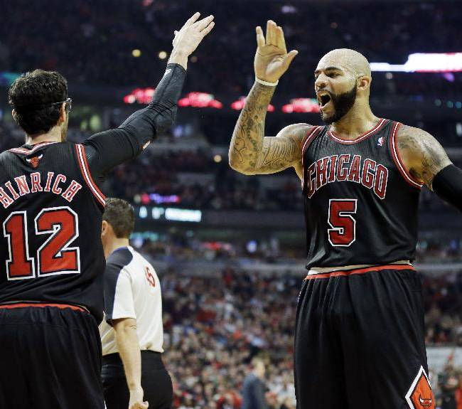 Chicago Bulls guard Kirk Hinrich (12) celebrates with forward Carlos Boozer after scoring a basket during the second half of an NBA basketball game against the New York Knicks in Chicago, Thursday, Oct. 31, 2013. The Bulls won 82-81
