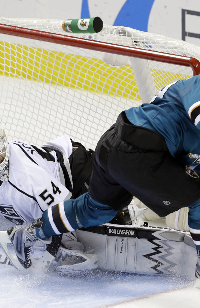 San Jose Sharks' Joe Thornton, right, scores past Los Angeles Kings goalie Ben Scrivens (54) during the eighth round of the shootout in an NHL hockey game Wednesday, Nov. 27, 2013, in San Jose, Calif. San Jose won 3-2