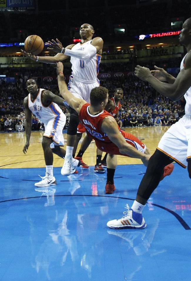 Oklahoma City Thunder guard Russell Westbrook (0) collides with Los Angeles Clippers forward Blake Griffin (32) while going up for a shot in the first quarter of an NBA basketball game in Oklahoma City, Thursday, Nov. 21, 2013