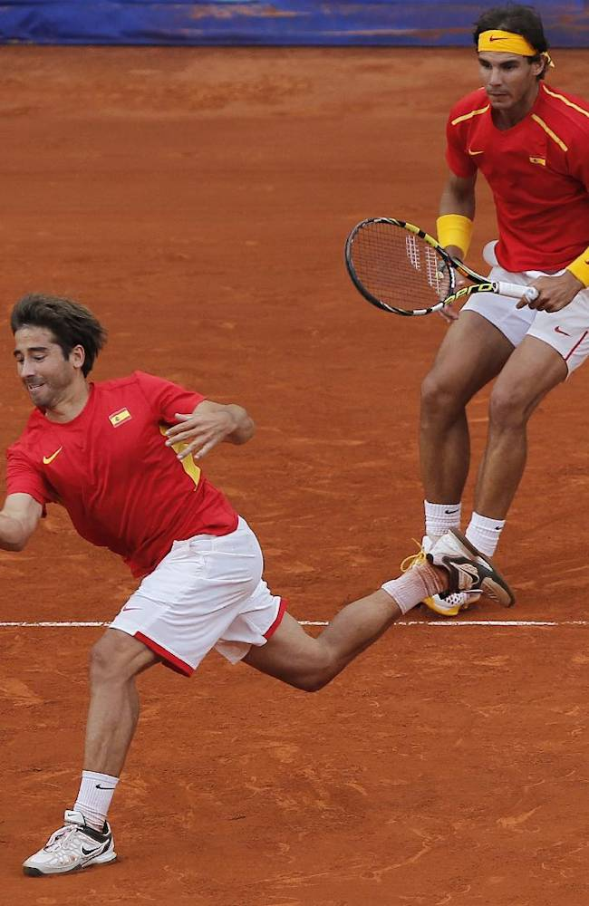 Spain's Marc Lopez, left, returns the ball as partner Rafael Nadal looks on during their doubles match against Ukraine's Denys Molchanov and Sergiy Stakhovsky on the second day of the World Group play-off Davis Cup tennis in Madrid, Spain, Saturday, Sept. 14, 2013