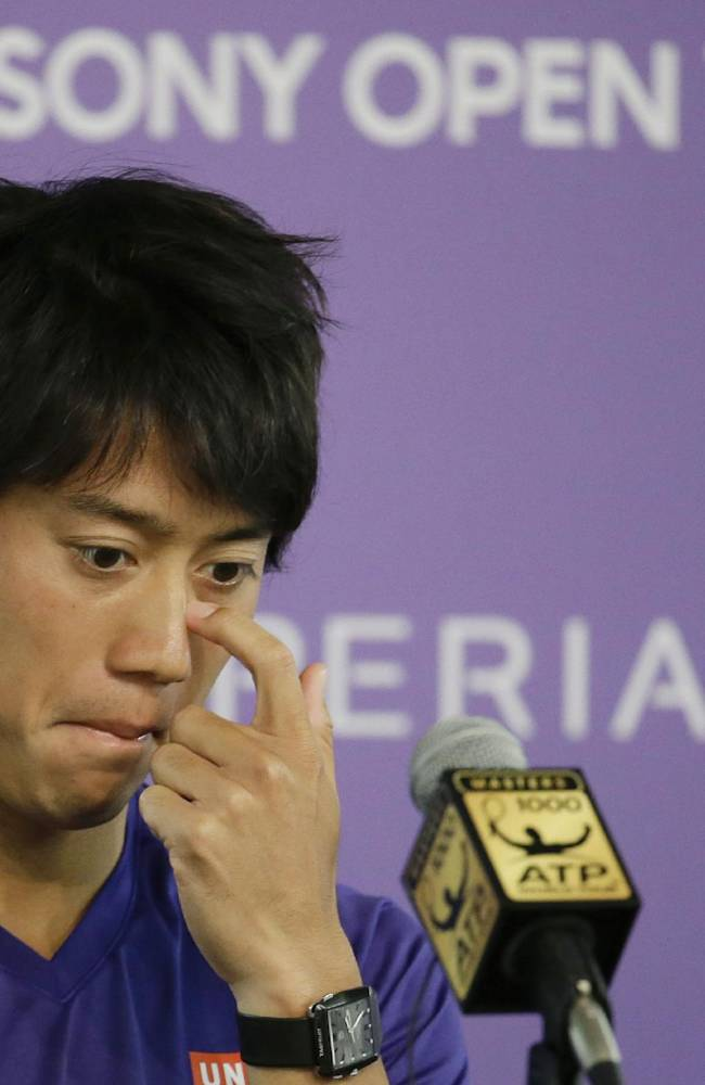 tKei Nishikori, of Japan, looks down at a news conference after withdrawing from his semifinal match against Novak Djokovic due to a left groin injury at the Sony Open tennis tournament, Friday, March 28, 2014, in Key Biscayne, Fla