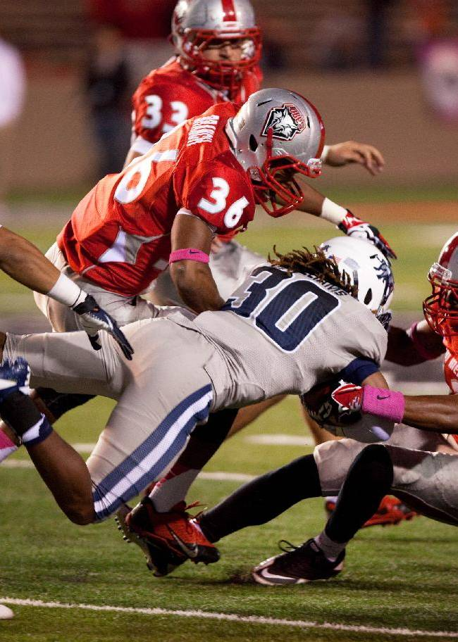 Utah State running back Kennedy Williams (30) is taken down by the New Mexico defense in the second half of an NCAA college football game, Saturday, Oct. 19, 2013, at University Stadium in Albuquerque, N.M. Utah State won 45-10