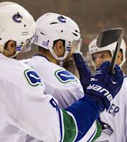 Vancouver Canucks' Ryan Kesler, center, celebrates with teammates Chris Tanev, left, and Jannik Hansen of Denmark, after scoring a goal during the first period of an NHL hockey game against the Philadelphia Flyers, Tuesday, Oct. 15, 2013, in Philadelphia. (AP Photo/Chris Szagola)