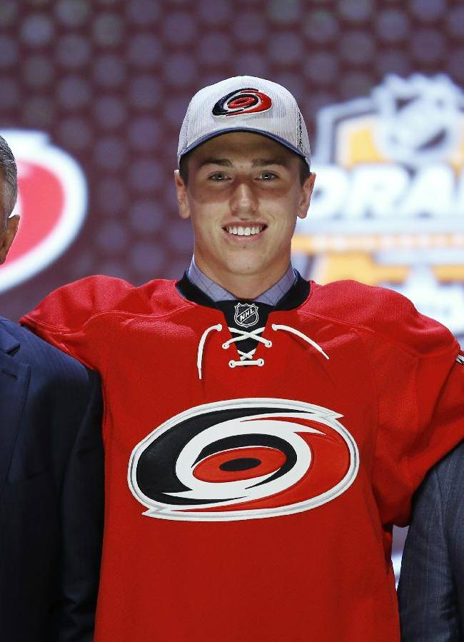 Haydn Fleury stands with Carolina Hurricanes officials after being chosen seventh overall during the first round of the NHL hockey draft, Friday, June 27, 2014, in Philadelphia