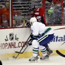 Vancouver Canucks defenseman Chris Tanev (8) boards Washington Capitals right wing Troy Brouwer (20) in the second period of an NHL hockey game, Tuesday, Dec. 2, 2014, in Washington The Associated Press