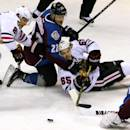 Colorado Avalanche defenseman Zach Redmond (22) wrestles with Chicago Blackhawks center Andrew Shaw (65) in front of Avalanche goalie Calvin Pickard (31) as Blackhawks left wing Brandon Saad (20) looks on in the first period of an NHL hockey game in Denver, Saturday, Dec. 27, 2014. (AP Photo/Joe Mahoney)