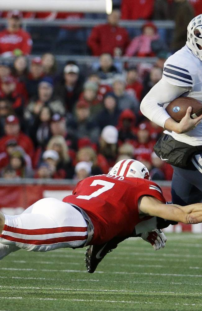Brigham Young's Taysom Hill, right, tries to break away from Wisconsin's Michael Caputo during the first half of an NCAA college football game on Saturday, Nov. 9, 2013, in Madison, Wis