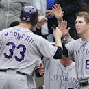 Colorado Rockies' Justin Morneau is met by Corey Dickerson, right, and others after scoring against the San Diego Padres during the seventh inning of a baseball game Thursday, April 17, 2014, in San Diego The Associated Press