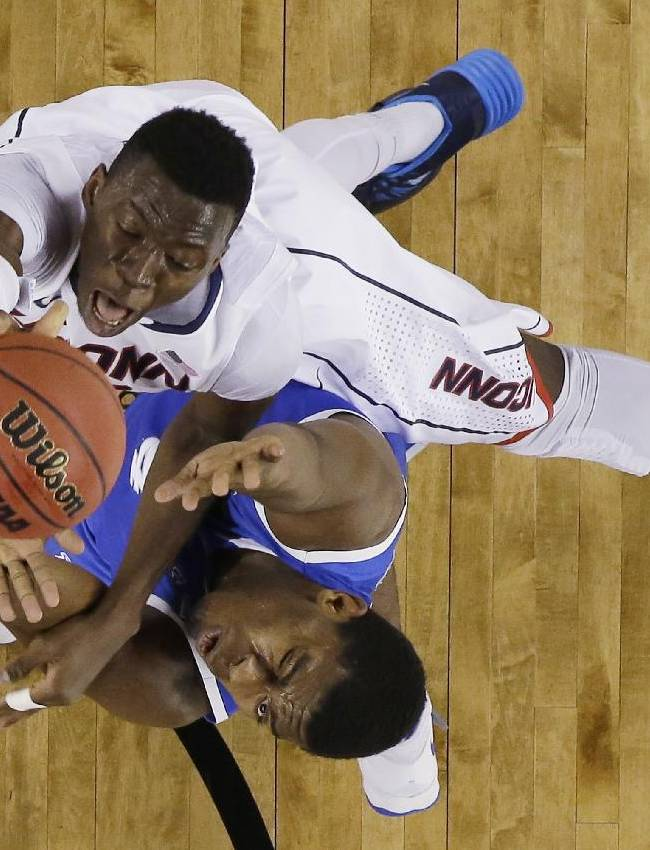 Connecticut center Amida Brimah, top, shoots over Kentucky center Dakari Johnson during the first half of the NCAA Final Four tournament college basketball championship game Monday, April 7, 2014, in Arlington, Texas