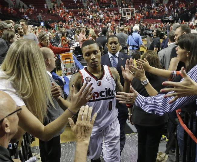 Portland Trail Blazers' Damian Lillard (0) walks off the court as fans reach for him following Game 4 of a Western Conference semifinal NBA basketball playoff series against the San Antonio Spurs, Monday, May 12, 2014, in Portland, Ore. The Trail Blazers won 103-92