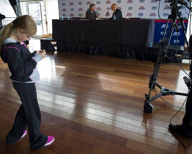 Lainee Mack, daughter of Xavier head coach Chris Mack, who is being interviewed at right in background, looks at an electronic device on the floor of the interview set at the Big East Conference NCAA college basketball media dayin New York, Wednesday, Oct. 16, 2013
